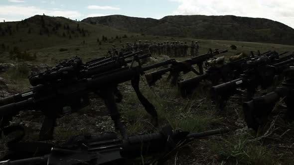 Thumbnail for Assault rifles in foreground with group of soldiers in background.