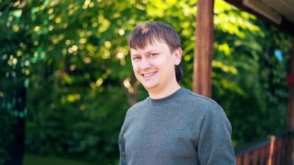 Thumbnail for Nahaufnahme, Porträt: Junger Mann steht auf dem Hintergrund eines Sommerhauses und Grün und Lächeln