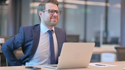 Businessman with Laptop having Back Pain in Office