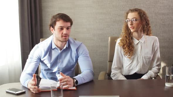 Thumbnail for Two Cheerful Office Workers Sitting at Conference Table