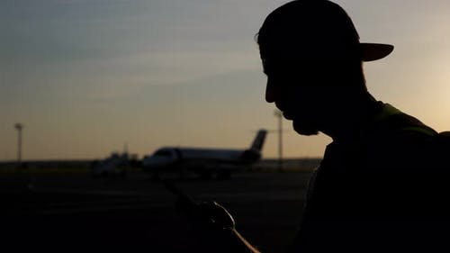 Unrecognizable Man Browsing Mobile Phone on Airfield with Plane on Background.
