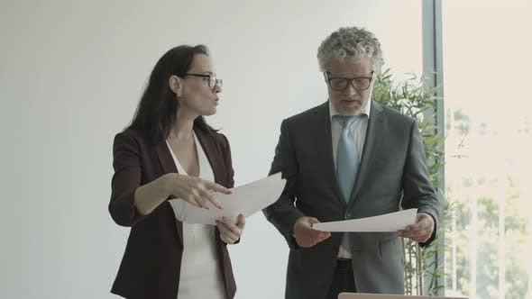 Thumbnail for Grey Haired Male Boss Giving Documents To Assistant