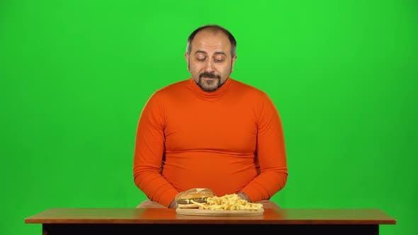 Thumbnail for Caucasian Man will einen Burger und Pommes Frites essen, ungesunde Nahrung aber wählen Sie einen Apfel, Grün