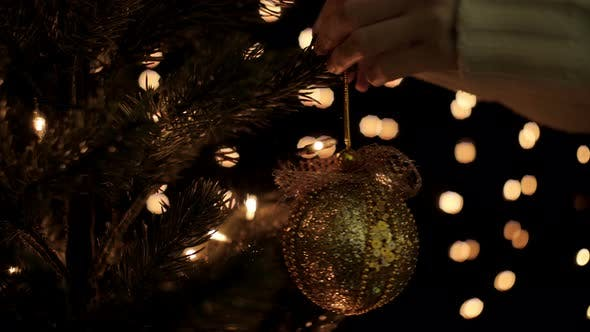 Thumbnail for Woman Hanging Christmas Ball On Tree