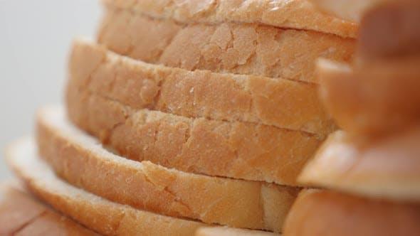 Thumbnail for White toasting bread pieces bunch food background slow tilt 4K 2160p 30fps UltraHD video - Slow tilt