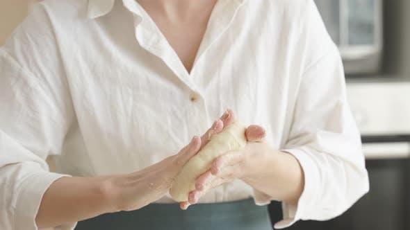 Closeup of Women's Hands Rolling Out Pizza Dough