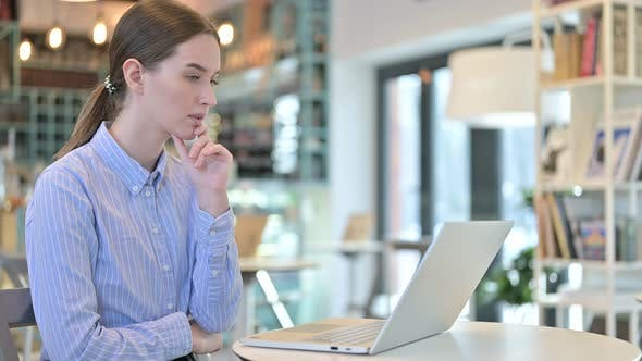 Thumbnail for Thoughtful Young Businesswoman Using Laptop in Cafe