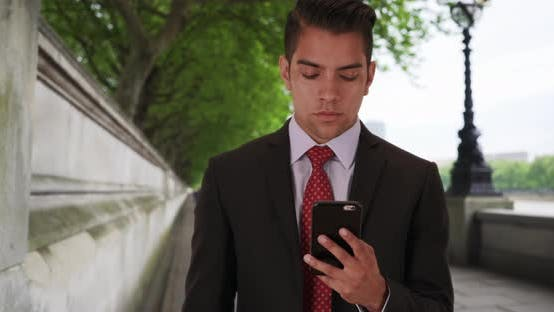 Cover Image for Latino businessman text messaging on mobile phone by River Thames