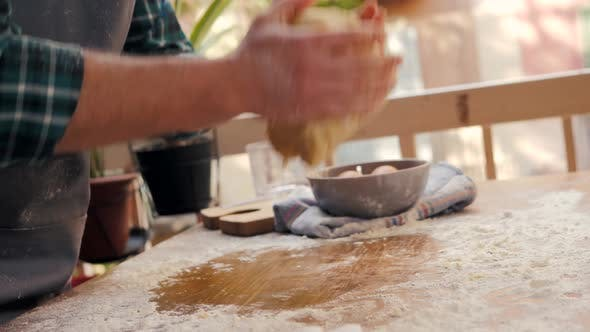 Male Hands Clapping and Sprinkling White Flour Over Dough on Kitchen