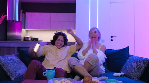 Thumbnail for Slow Motion Happy Young People Playing Video Games Console While Sitting Couch Front Tv