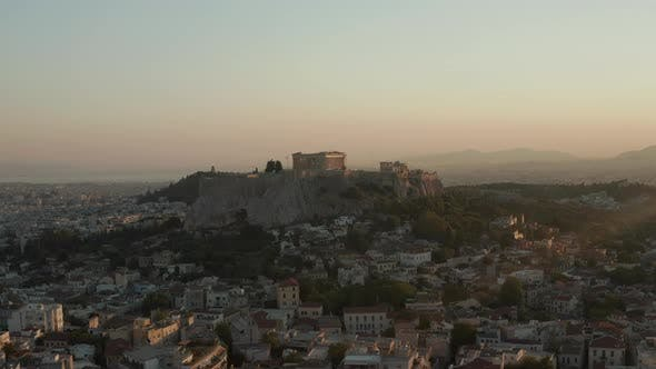 Slow Aerial Dolly Towards Mountain with Acropolis of Athens in Greece in Beautiful Golden Hour