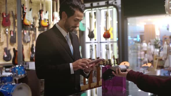 Thumbnail for A Middle Eastern Man Using Mobile Phone To Purchase Product