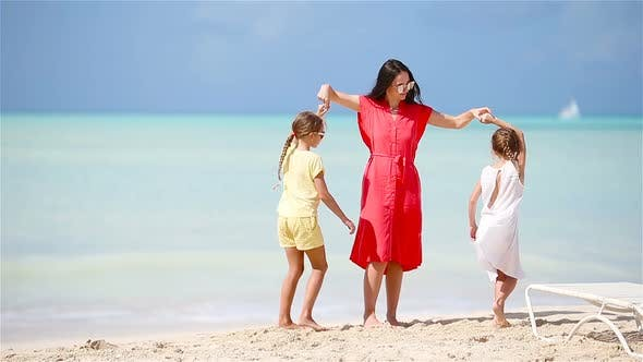 Thumbnail for Adorable Little Girls and Young Mother Having Fun on White Beach
