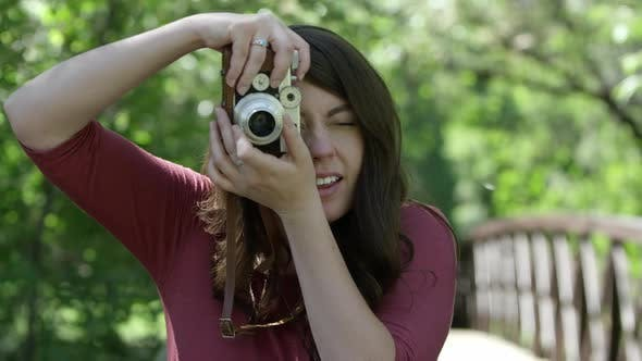Young woman taking photo with vintage film camera