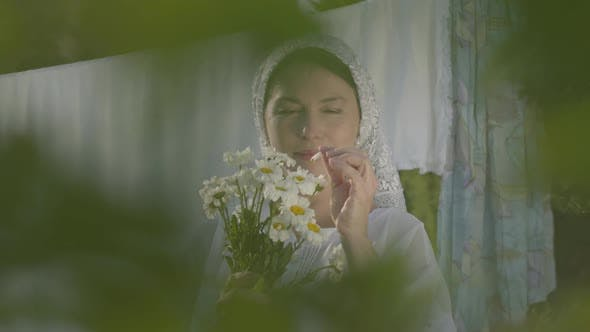 Thumbnail for Attractive Senior Woman with White Shawl on Her Head Tears Off Daisy Petals at the Clothesline