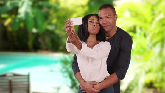 Thumbnail for Black couple on vacation in Caribbean taking selfie together by a pool