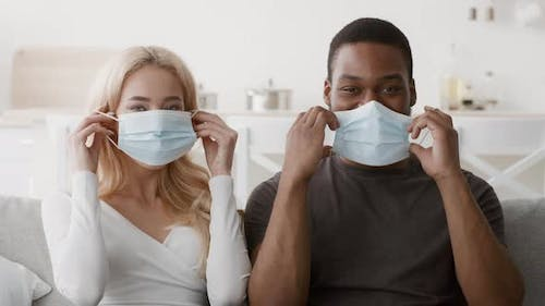 Smiling Diverse Couple Putting On Protective Face Masks At Home