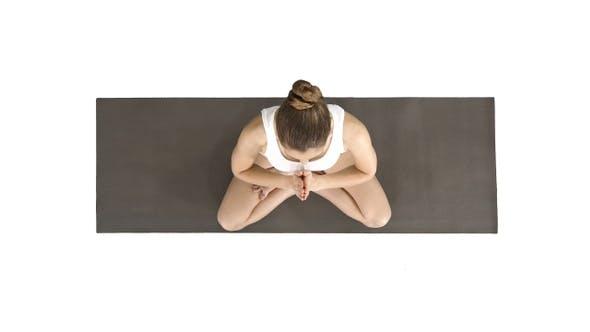 Young yogi woman practicing yoga making namaste gesture