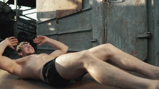 Muskulöser Mann macht Übungen für Bauchmuskeln im Freien. Zeitlupe. Konzept von Motivation und Sport
