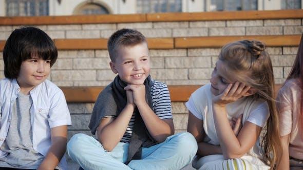 Thumbnail for Niedliche kleine Kinder sitzen auf einer Bank, Glückliche Kindheit