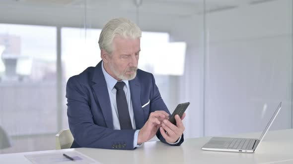 Old Businessman Using Smartphone in Modern Office