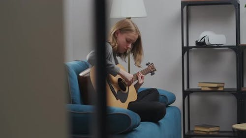 A Teenage Girl in a Gray Sweatshirt Plays Quiet Music on an Acoustic Guitar in Her Free Time