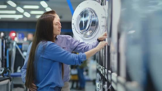 Thumbnail for Young Married Couple Man and Woman in Appliances Store Choose To Buy a Washing Machine for the House