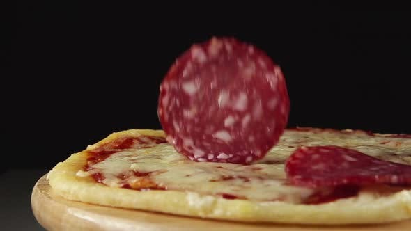 Thumbnail for Salami Slices Fall On A Rotating Pizza On A Black Background