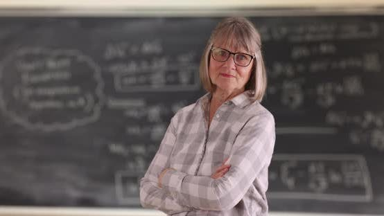 Thumbnail for Confident senior woman teacher with arms crossed standing in front of chalkboard