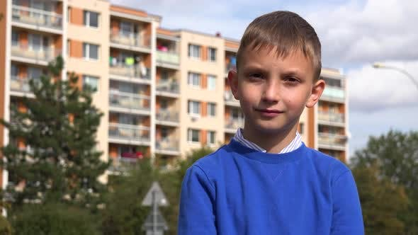 Thumbnail for A Young Boy Smiles at the Camera at an Apartment Complex