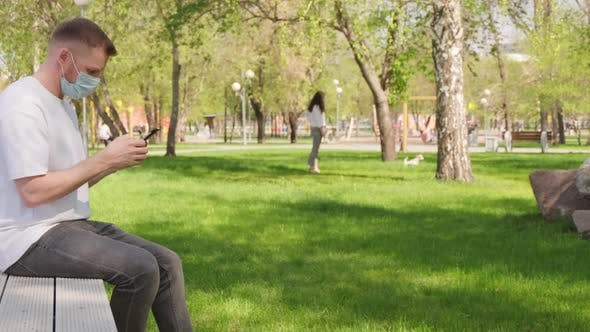Thumbnail for Man in Face Mask Resting on Bench in Park during Pandemic