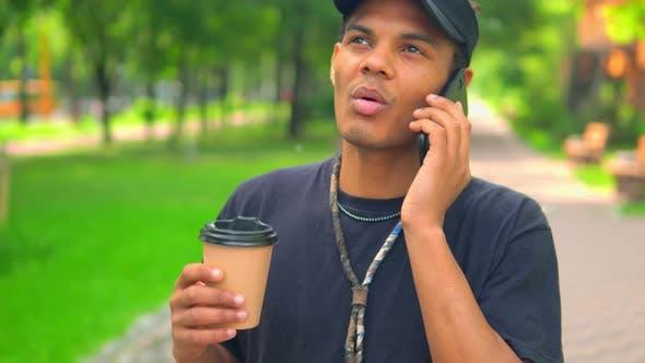 Thumbnail for Mixed Race Kerl trinken Kaffee sprechen per Telefon