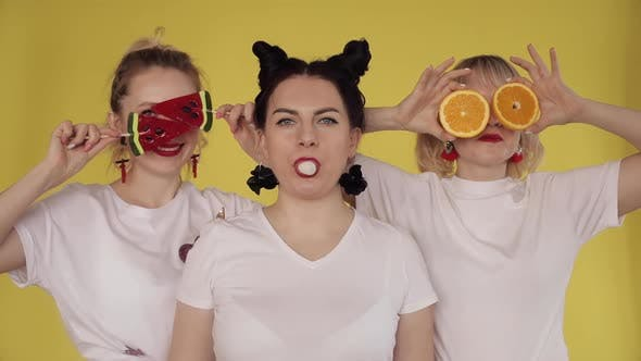 Thumbnail for Three Girls Having Fun on Yellow Background. Chewing Gum, Playing with Candies and Fruit.