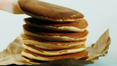 Another pancake is placed on a stack of pancakes