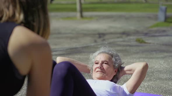 Thumbnail for Smiling Senior Woman Preparing To Do Abdominal Crunches in Park
