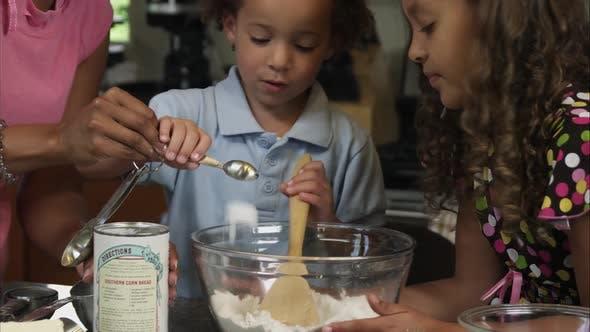 Slow motion pan of boy helping pour in baking powder