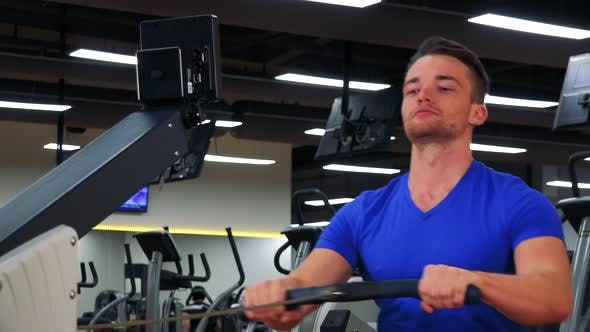 Thumbnail for A Young Fit Man Trains on a Rowing Machine in a Gym - Closeup