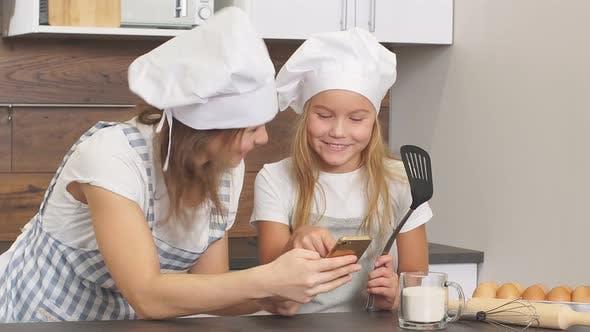 Schöne Mutter und Tochter schauen sich mit Liebe zum Backen in der Küche an