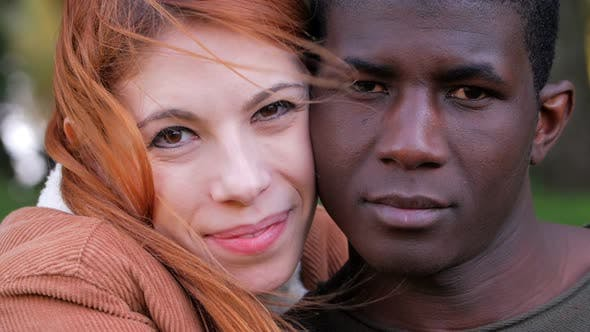 Portrait Of young attractive Happy Mixed Race Couple in the park