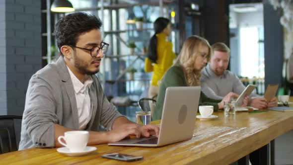Cover Image for Middle-Eastern Businessman Working on Laptop in Coffeeshop