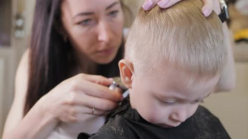 Young Mom Hairdresser Cuts Her Baby Boy at Home with Hair Clipper During Quarantine