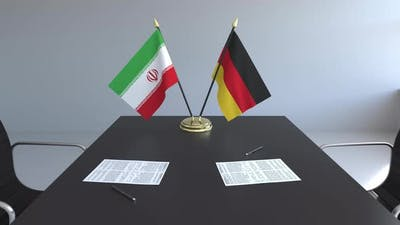 Flags of Iran and Germany and Papers on the Table