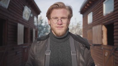 Portrait of a Handsome Bearded Guy with Glasses Dressed in a Warm Sweater and Jacket