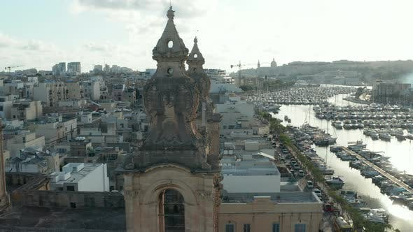 Thumbnail for Close Up of Two Church Bell Towers on Malta with Sailboats and Yacht Port in Background on Beautiful