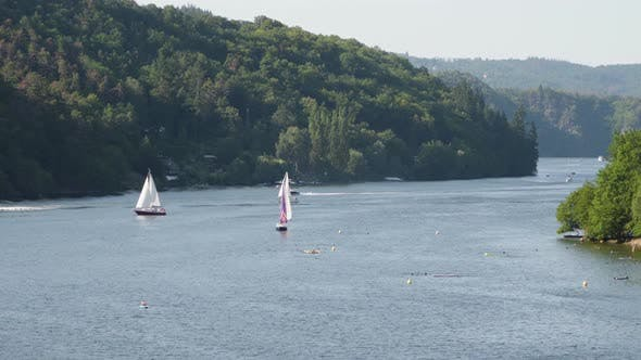 Thumbnail for Yachts Float on a Lake, People Swim By the Coast, Speed Boat Passes By