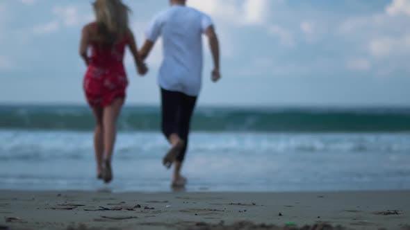 Thumbnail for Laufen in Richtung der Wellen Junges hübsches Paar im Freien auf dem malerischen schönen Meer Strand auf