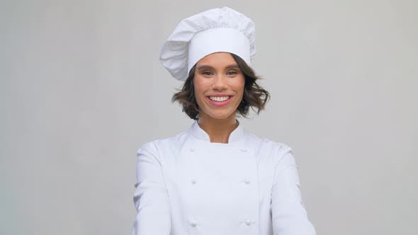 Smiling Female Chef in Toque Showing Thumbs Up