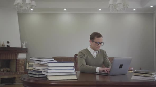 Thumbnail for Portrait Adorable Young Man in Glasses Sitting at the Wooden Table in the Office