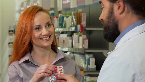 Cover Image for Beautiful Woman Receiving Pills From Her Pharmacist, Shopping at Drugstore