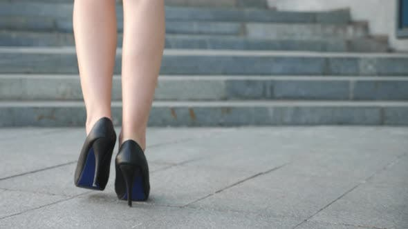 Female Legs in High Heels Shoes Walking on the Stairs. Feet of Businesswoman Stepping Up on Stairway